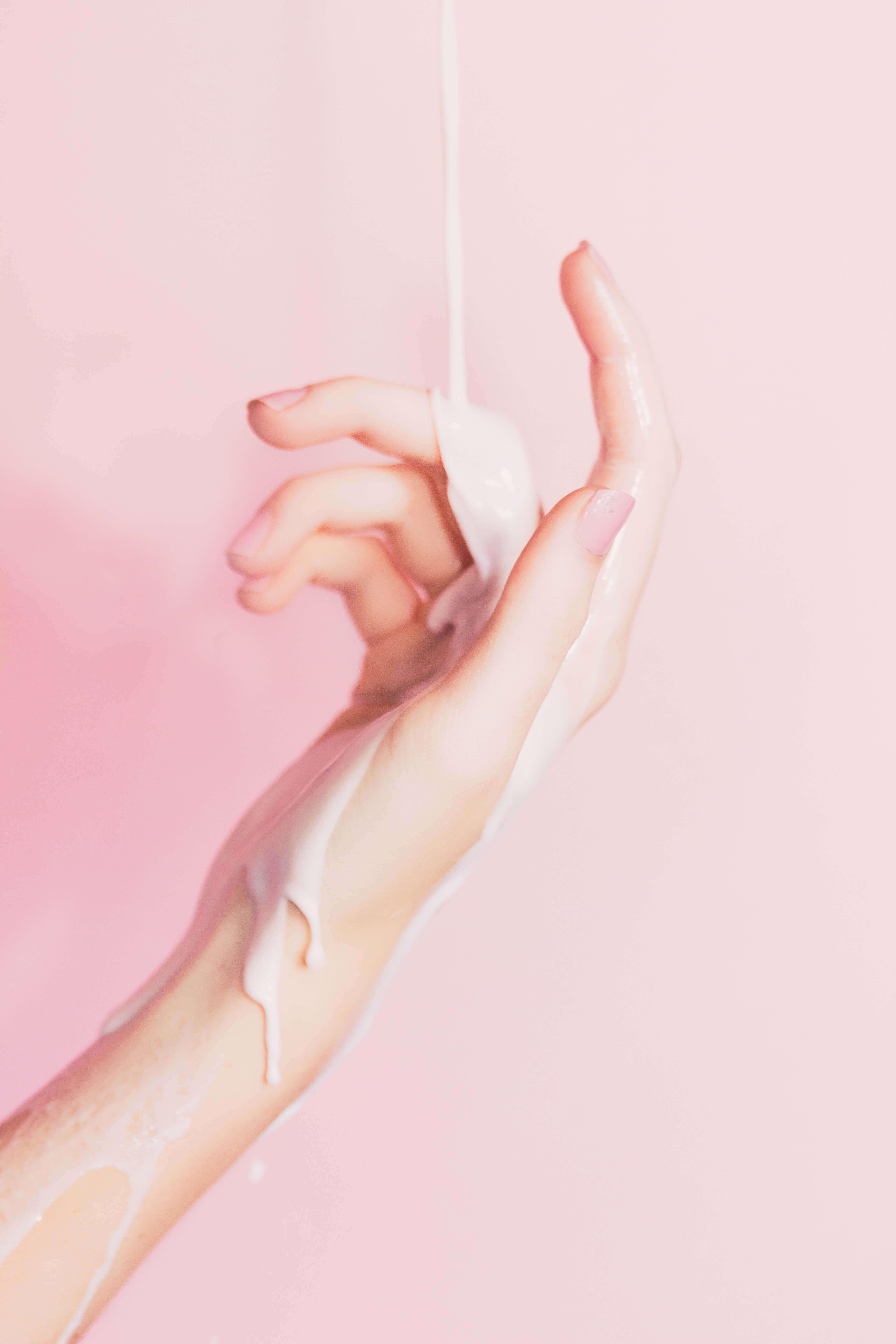 Winterpflege Creme läuft über eine Hand mit schönen Fingernägeln in Rosa. Im Hintergrund eine passende Rosafarbene Wand